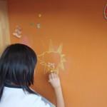 壁にチョークでお絵かきをしています。