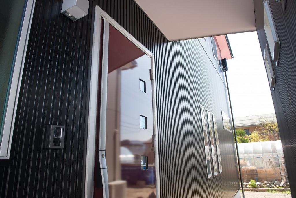 黒色の外壁に、パールボルドー色の玄関ドア